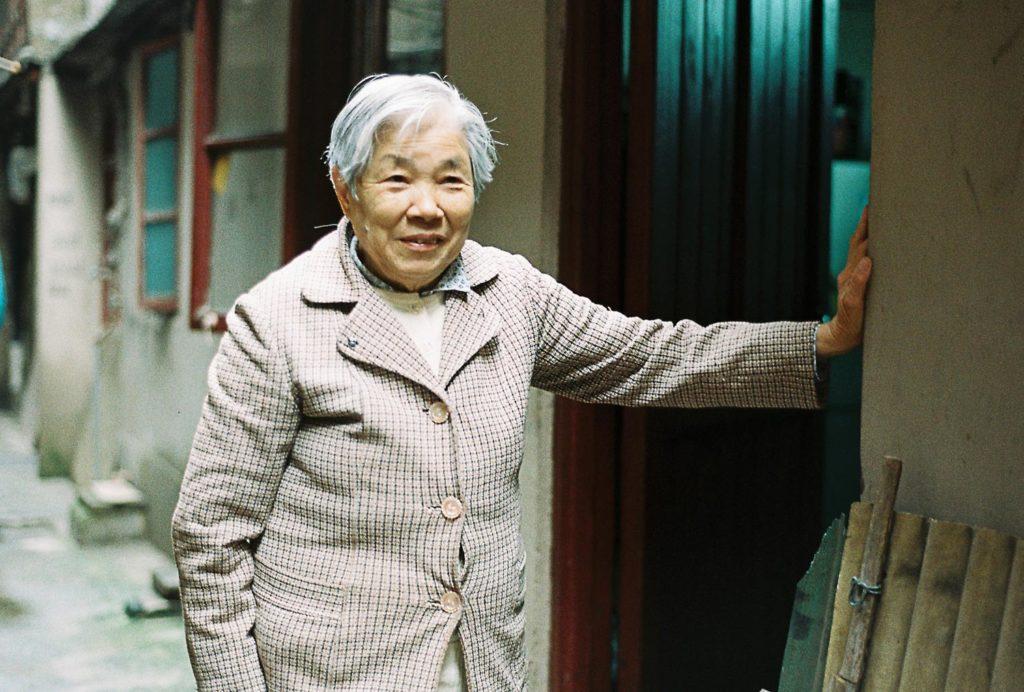 Mulher chinesa antiga na porta da sua casa