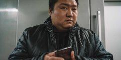 Homem chinês desconfiado com o seu celular na mão